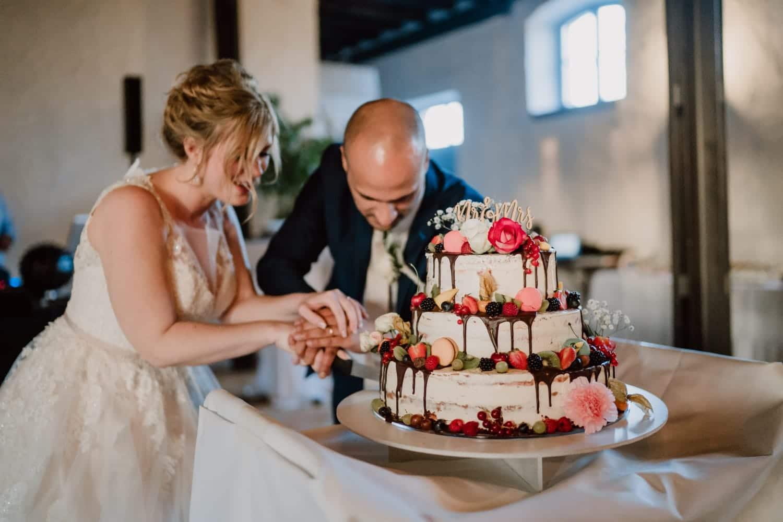 Moni und Thomas beim Anschneiden der Hochzeitstorte - Photo by Tina Rösler